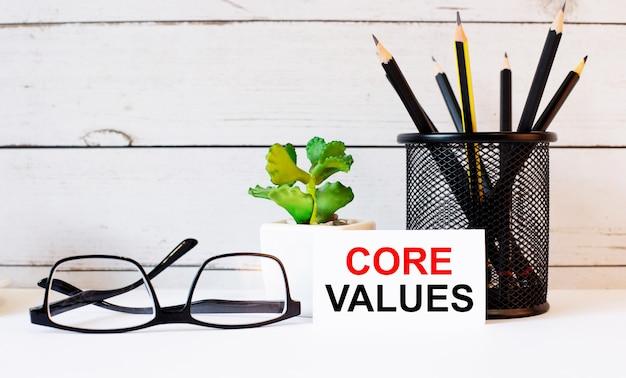 Na área de trabalho estão relatórios, gráficos, uma caneta vermelha, um marcador preto, um bloco de notas vermelho e uma folha de papel branca com o texto valores centrais. conceito de negócios
