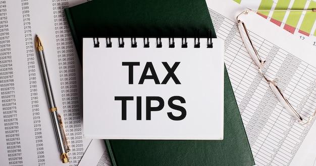 Na área de trabalho estão relatórios, óculos, uma caneta, um diário verde e um caderno branco com as palavras dicas de imposto