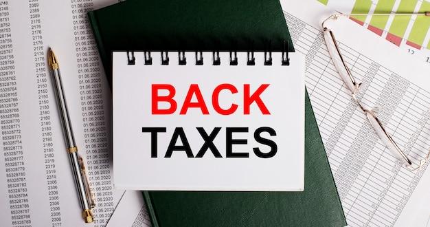 Na área de trabalho estão relatórios, óculos, uma caneta, um diário verde e um caderno branco com as palavras tras impostos