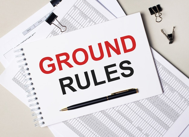 Na área de trabalho há documentos, caneta, clipes de papel pretos e um caderno com o texto regras principais