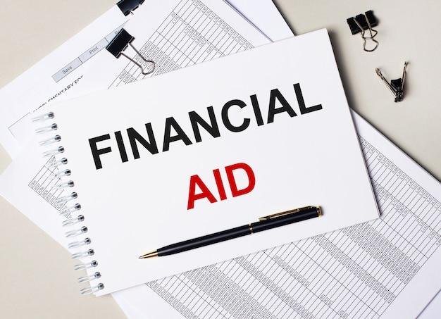 Na área de trabalho há documentos, caneta, clipes pretos e um caderno com o texto ajuda financeira. conceito de negócios