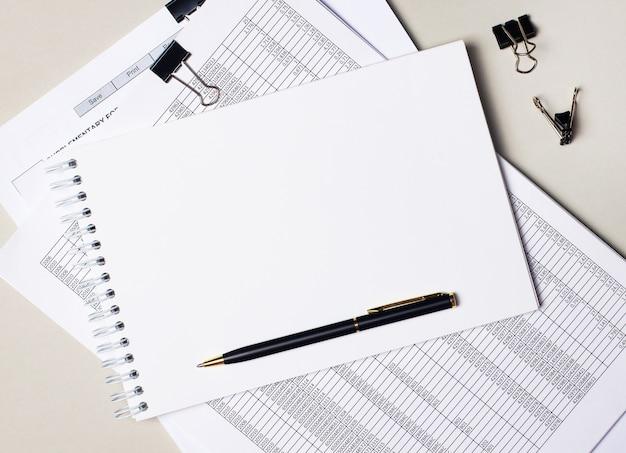Na área de trabalho há documentos, clipes de papel pretos e um caderno em branco com um local para inserir texto