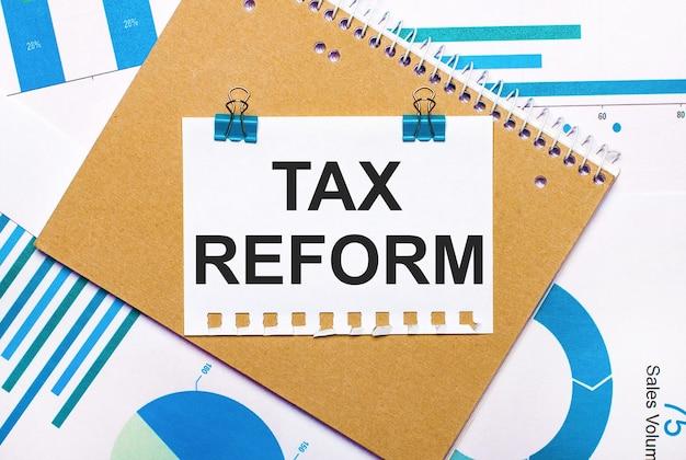 Na área de trabalho há gráficos e diagramas em azul e azul claro, um caderno marrom e uma folha de papel com clipes azuis e texto de reforma tributário.