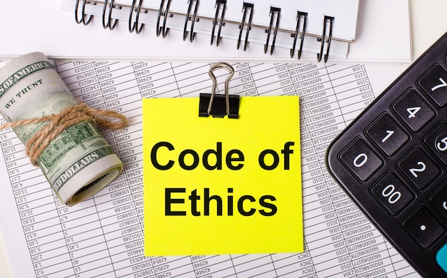 Na área de trabalho há relatórios, blocos de notas, calculadora, dinheiro e um adesivo amarelo com o texto código de ética. conceito de negócios