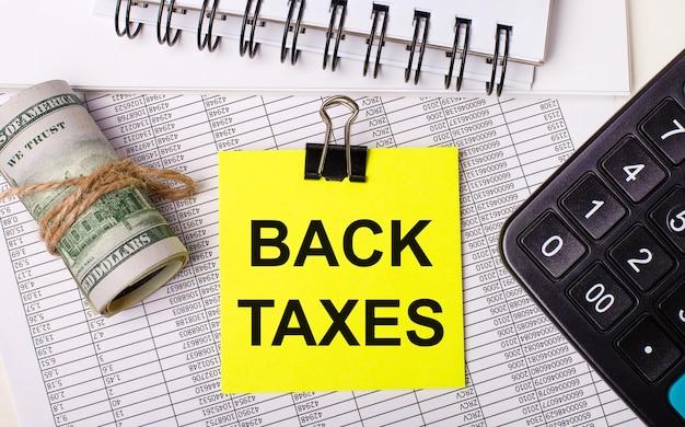 Na área de trabalho há relatórios, blocos de notas, calculadora, dinheiro e um adesivo amarelo com o texto devolução de impostos. conceito de negócios