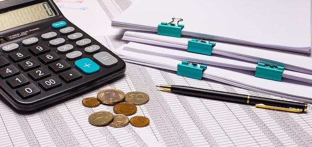 Na área de trabalho há relatórios, calculadora, dinheiro e caneta