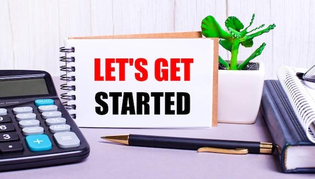 Na área de trabalho há uma calculadora, diários, um vaso de plantas, uma caneta e um caderno com o texto começando. conceito de negócios. local de trabalho de perto