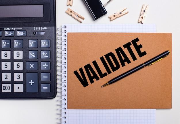 Na área de trabalho há uma calculadora, uma caneta e prendedores de roupa próximos a um caderno com o texto validar. conceito de negócios. vista de cima