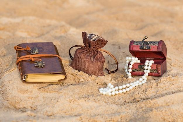 Na areia há um livro encadernado em couro, um saco de areia e um baú de pérolas
