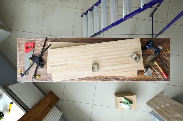 Na bancada existem ferramentas e folhas folheadas a madeira