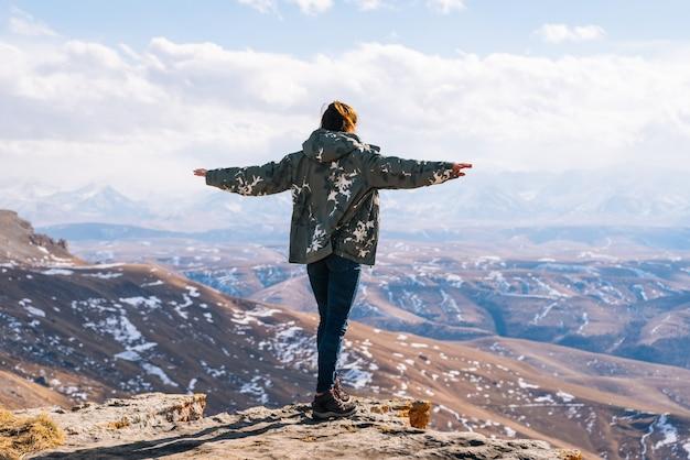 Na beira de um penhasco está uma turista no fundo das montanhas