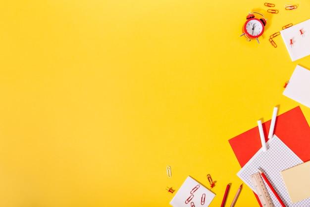 Na borda de uma parede amarela, lápis, papéis, clipes de rato e relógios estão caoticamente e lindamente
