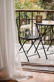 Na cadeira está um buquê da noiva. mesa e cadeira na varanda