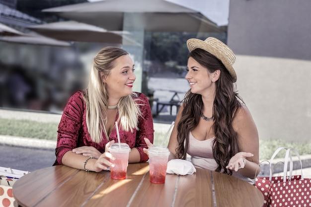 Na cafeteria. mulheres felizes e encantadas conversando umas com as outras sentadas à mesa no refeitório