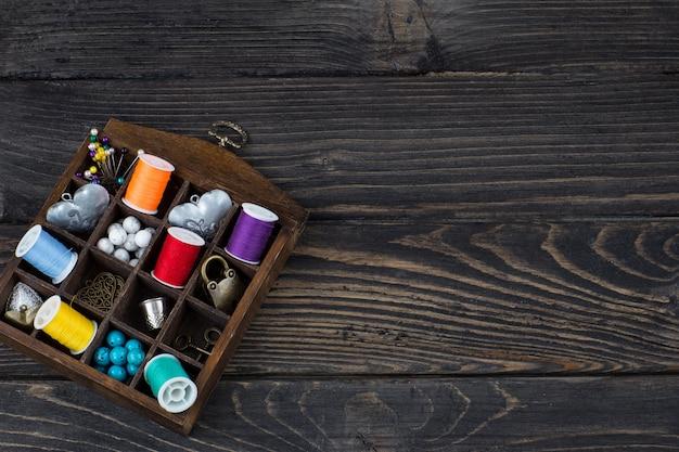 Na caixa são meadas coloridas de fios, miçangas, botões, agulhas