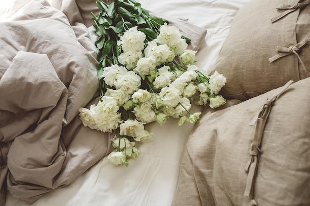 Na cama desarrumada, um grande buquê de roupas brancas