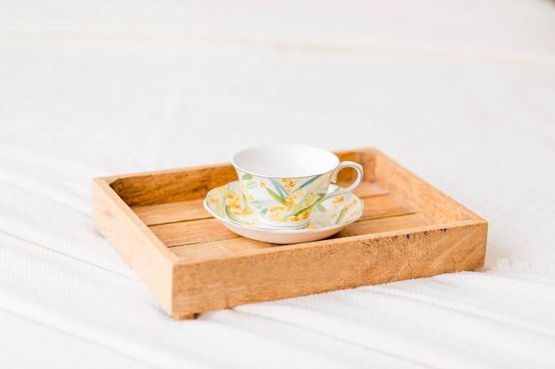 Na cama está uma bandeja de madeira com uma xícara e café. foto