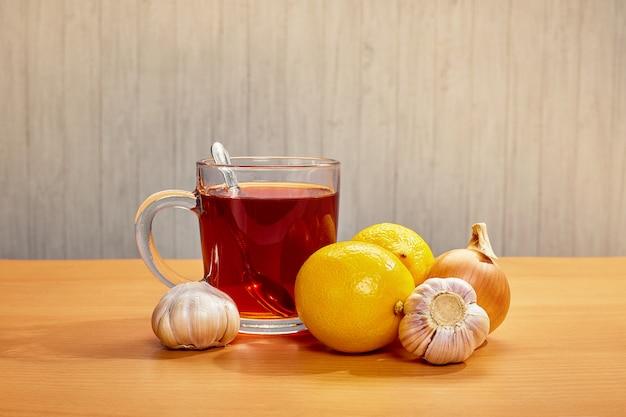 Na caneca de mesa com limões de chá cebolas alho