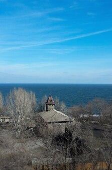 Na costa do mar frio, há uma velha casa de madeira com prédios ao fundo
