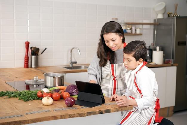 Na cozinha, uma família de pais solteiros cozinhando mãe e filho em busca de uma receita de culinária online v ...