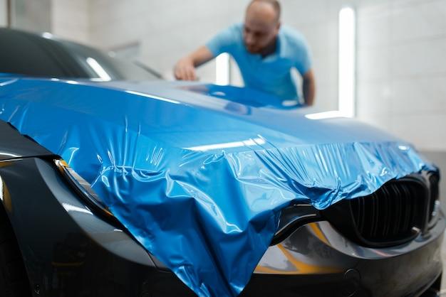 Na embalagem do carro, o homem instala uma película protetora de vinil ou filme no capô. trabalhador faz detalhamento de automóveis