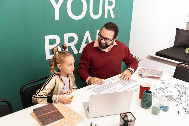 Na escola. professor de cabelos escuros, barbudo e sorridente, usando óculos, explicando o novo material para seu aluno
