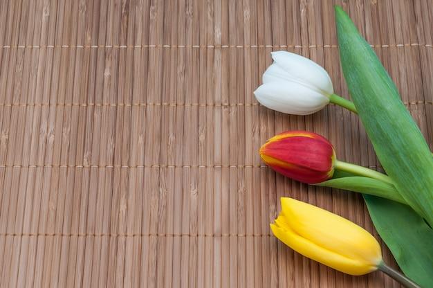 Na esteira de bambu do lado direito há três tulipas vermelhas amarelas e brancas.