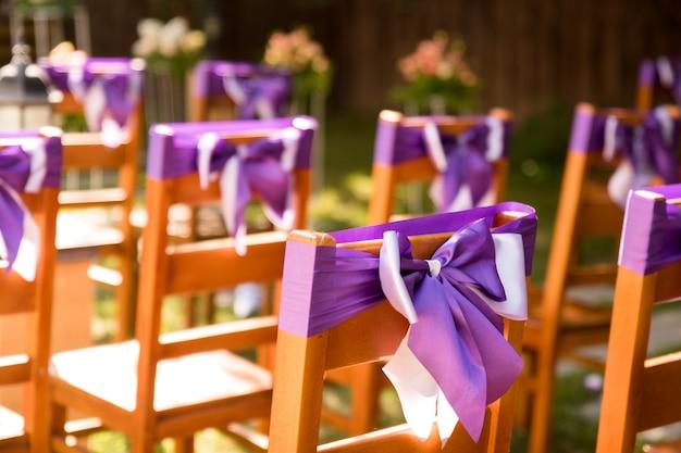 Na foto vemos cadeiras decoradas com fitas lilás lavanda. cerimônia de casamento ao ar livre