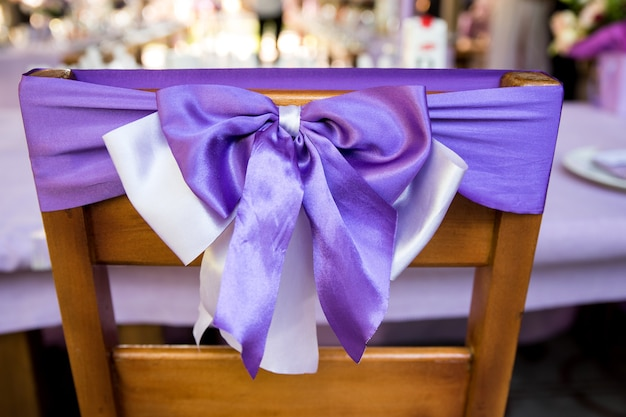Na foto vemos cadeiras decoradas com fitas lilás lavanda. cerimônia de casamento interno