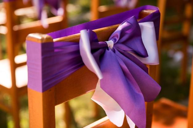Na foto vemos cadeiras decoradas com fitas lilás lavanda.