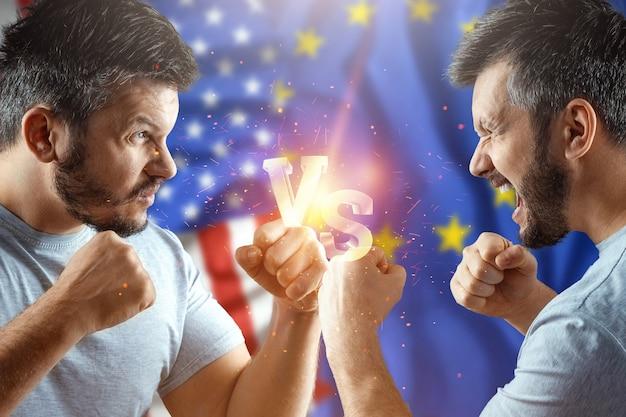 Na guerra comercial entre a união europeia e os estados unidos, dois homens estão se preparando para uma luta com a bandeira americana e a bandeira da união europeia. sanções, negócios.