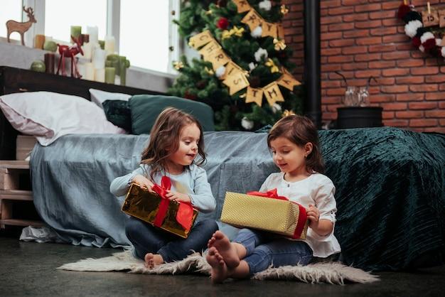 Na hora antes de abrir os presentes. férias de natal com presentes para essas duas crianças que estão sentadas dentro de casa no belo quarto perto da cama.