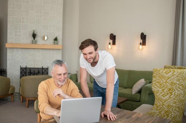 Na internet. dois homens na sala em frente ao laptop assistindo algo em um laptop