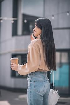 Na internet. linda jovem asiática segurando um smartphone nas mãos