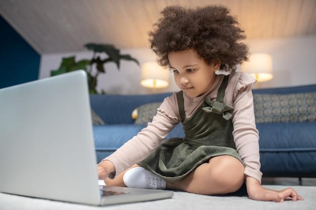 Na internet. menina afro-americana de cabelo encaracolado sentada perto do laptop no chão em casa, focada, interessada