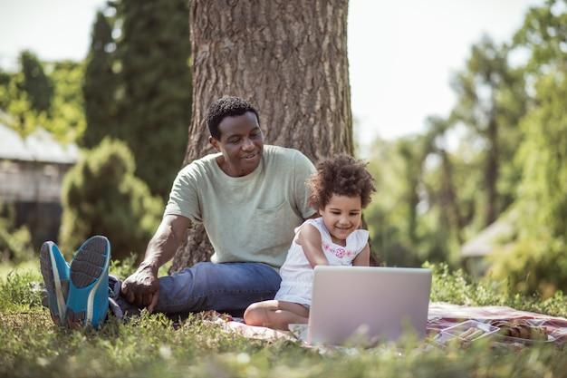 Na internet. menina de cabelos cacheados sentada sob uma árvore com o pai e assistindo algo online
