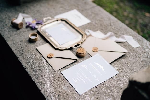 Na laje de pedra estão envelopes lacrados com cera, uma bandeja de metal, fitas e cartões postais