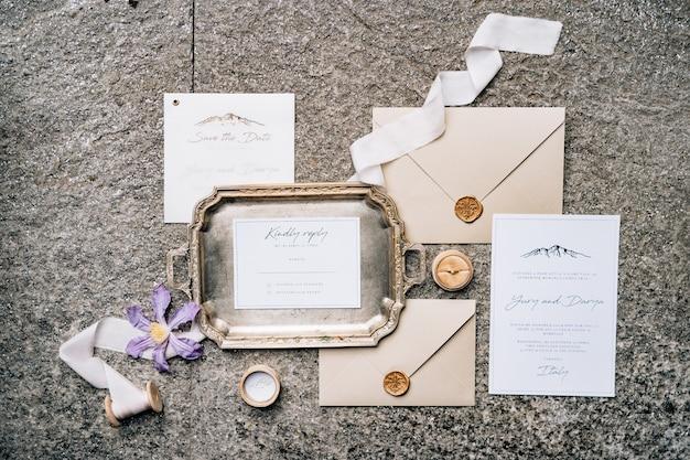 Na laje de pedra estão envelopes lacrados com cera, uma bandeja de metal, fitas, flores e cartões postais, vista superior