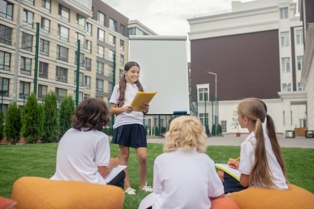Na lição. uma garota com uma camisa branca em pé no flipchart e lendo algo em voz alta