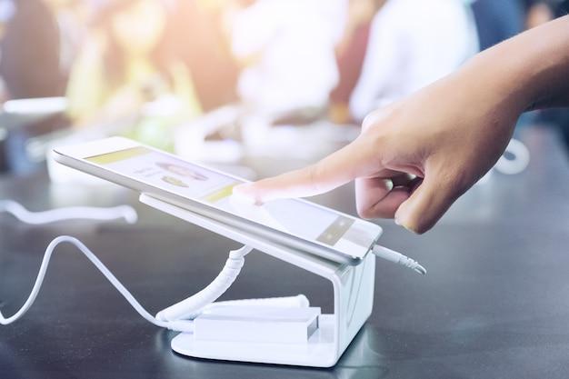Na loja de móveis o cliente assume tablet digital de tela, em pé no celular e tablet