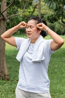 Na manhã. dor de cabeça asiática da mulher sênior durante o exercício no parque.
