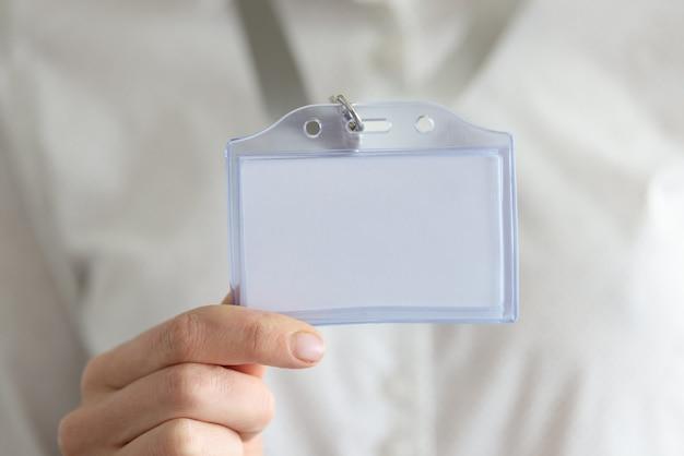 Na mão da mulher há um distintivo branco vazio