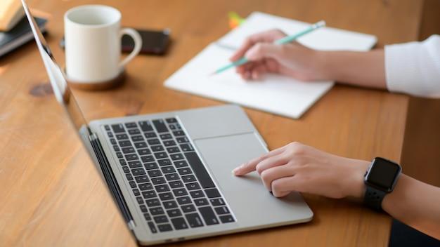 Na mão de uma jovem mulher usando um laptop e escrevendo um relatório, ela trabalha em casa.