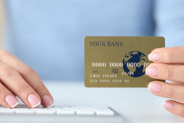 Na mão de uma mulher, cartão de banco de crédito de plástico e teclado. conceito de pagamentos seguros pela internet