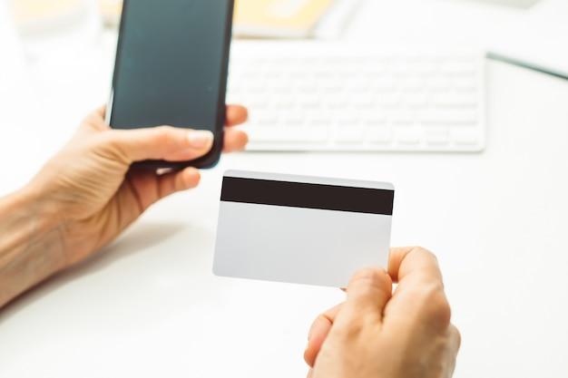 Na mão é um cartão de crédito em branco branco e telefone móvel para pagamento pela internet.