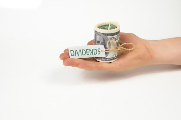 Na mão estendida na palma de um maço retorcido de notas de cem dólares com o rótulo dividendos, sobre fundo branco, isolado
