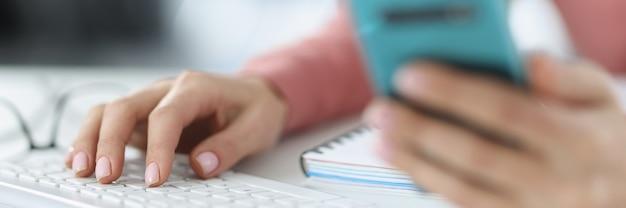 Na mão feminina, um smartphone e uma segunda mão em aplicativos de smartphone de teclado de computador para