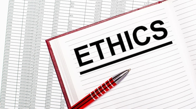 Na mesa ao lado dos relatórios está um diário com o texto ética. perto está uma alça vermelha.