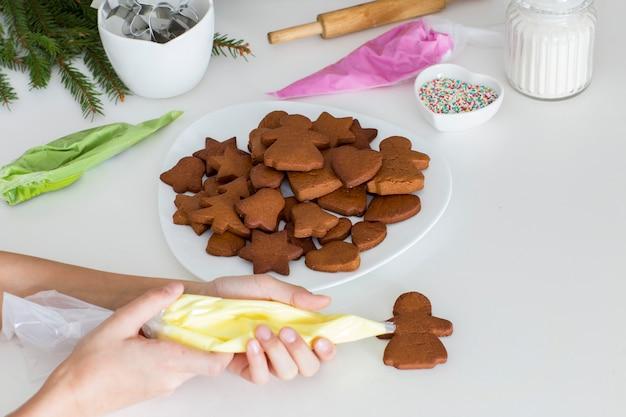 Na mesa da cozinha em um prato biscoitos de gengibre, ramos de abeto, farinha, geada, açúcar e mãos de um menino que decora biscoitos