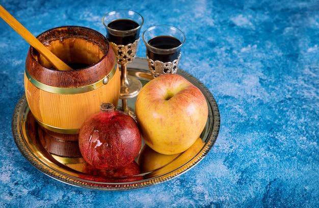 Na mesa da sinagoga estão os símbolos de maçã e romã de rosh hashaná